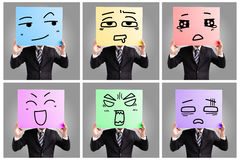 Businessman holding many expressions billboards Stock Images