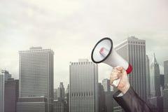 Businessman holding megaphone on cityscape Royalty Free Stock Image