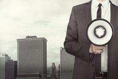 Businessman holding megaphone on cityscape Stock Images