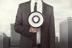 Businessman holding megaphone on cityscape Royalty Free Stock Images