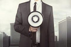 Businessman holding megaphone on cityscape Royalty Free Stock Images