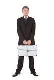 Businessman holding metal suitcase Stock Photos