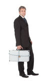 Businessman holding metal suitcase Stock Photos