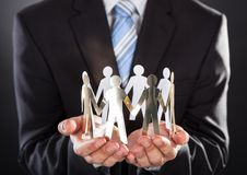 Businessman holding metal team in cupped hands Royalty Free Stock Images