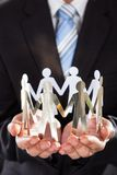 Businessman holding metal team in cupped hands Stock Images