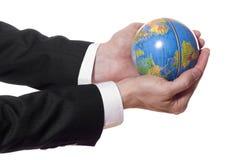 Businessman holding mini globe isolated on white Stock Image