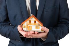 Businessman holding miniature house model Royalty Free Stock Images