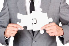 Businessman holding mismatch jigsaw. Businessman holding blank jigsaw isolated on white background with clipping path Stock Photography