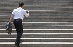 Businessman holding mobile and in hurry to run up on stairs. Young businessman holding mobile and in hurry to run up on stairs Royalty Free Stock Photos