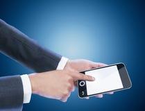 Businessman holding mobile phone. Blue background Stock Image