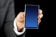 Businessman holding mobile phone with blue empty screen. Closeup of businessman holding mobile phone with blue empty screen. Over black background stock image