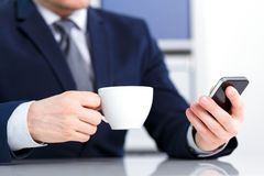 Businessman holding a mobile phone and coffee Stock Photography