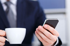 Businessman holding a mobile phone and coffee Royalty Free Stock Photography