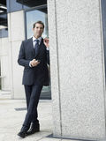 Businessman Holding Mobile Phone While Looking Away By Office Wall Royalty Free Stock Photo