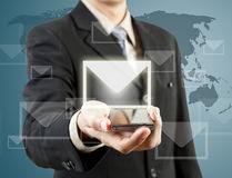Businessman holding mobile phone and mail Stock Photo