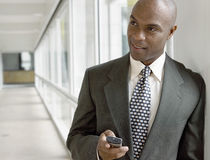 Businessman Holding Mobile Phone In Office Royalty Free Stock Photos