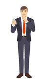 Businessman holding mobile phone and showing hush-hush sign Royalty Free Stock Image