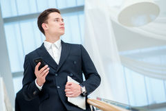 Businessman holding a mobile phone. Young businessman standing o. N the steps and keeps the tablet while it parnery talk to each other Stock Photography