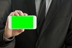Businessman holding mobile smart phone with green screen Stock Photos
