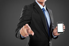 Businessman holding mobile smart phone and touching screen Stock Image