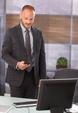 Businessman holding mobile. Businessman standing at desk in office, using mobilephone, dialing or writing text message Royalty Free Stock Images