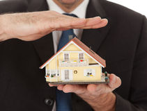 Businessman holding model of a house in hands Stock Photo