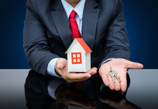 Businessman holding a model house and key Stock Photos