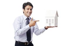 Businessman holding model house Royalty Free Stock Image