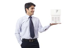 Businessman holding model house Royalty Free Stock Photo