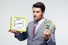 Businessman holding money and clock Royalty Free Stock Photo