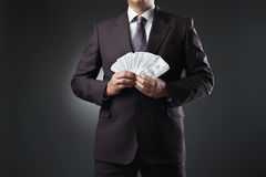 Businessman holding money in hands on dark Royalty Free Stock Image