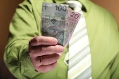 Businessman holding money 100 polish zloty Stock Images