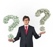 Businessman holding money question mark Stock Images