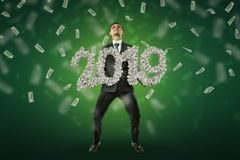 Businessman holding a `2019` money sign with US dollars in the air on green background. Banking and finance. Business success. Management and production royalty free stock photos