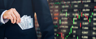 Businessman Holding money US dollar bills Business Financial con. Cept Forex graph of stock market on background Royalty Free Stock Image