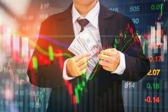 Businessman holding money us dollar bills on digital stock marke Royalty Free Stock Images
