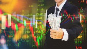 Businessman holding money us dollar bills on digital stock marke. T financial exchange information and trading graph background Royalty Free Stock Photography