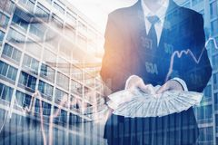 Businessman Holding money US dollar bills on digital stock marke. T financial exchange and Trading graph Double exposure city on the background Royalty Free Stock Photo