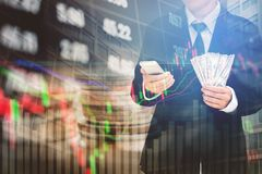 Businessman Holding money US dollar bills on digital stock marke. T financial exchange information and Trading graph background Stock Photos