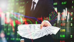Businessman Holding money US dollar bills on digital stock marke. T financial exchange information and Trading graph background Royalty Free Stock Photos
