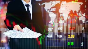 Businessman Holding money US dollar bills on digital stock marke. T financial exchange information and Trading graph background Stock Photo