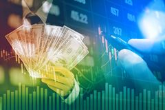 Businessman Holding money US dollar bills on digital stock marke. T financial exchange information and Trading graph background Stock Image