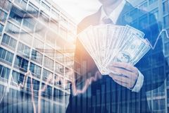 Businessman Holding money US dollar bills on digital stock marke. T financial exchange and Trading graph Double exposure city on the background Royalty Free Stock Images
