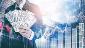 Businessman Holding money US dollar bills on digital stock marke. T financial exchange and Trading graph Double exposure city on the background Stock Photos