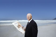 Businessman Holding Newspaper On Beach Royalty Free Stock Image