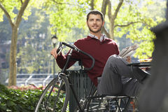 Businessman Holding Newspaper By Bicycle In Park. Happy young businessman holding newspaper by bicycle in park stock photos