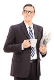 Businessman holding a newspaper and coffee Royalty Free Stock Photography