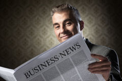 Businessman holding newspaper Stock Images