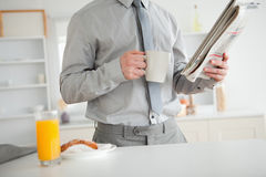 Businessman holding a newspaper while having breakfast Stock Photo