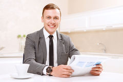 Businessman holding newspaper in kitchen Stock Images